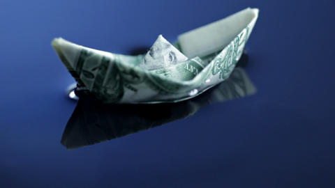 Origami boat made of dollar bill floating Stock Video Footage