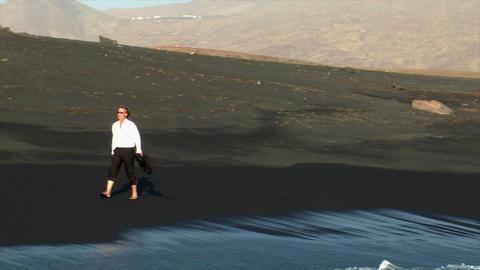 business man winking black lava beach Stock Video Footage