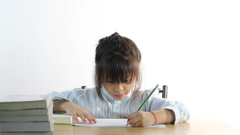 HD Dolly: cute girl writing homework on a book Footage