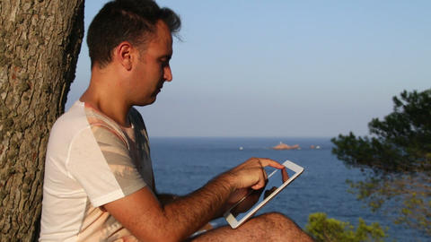 Browsing Tablet Next to the Seashore Panoramic Live Action