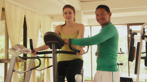 Personal Trainer With Young Woman In Wellness Gym Footage