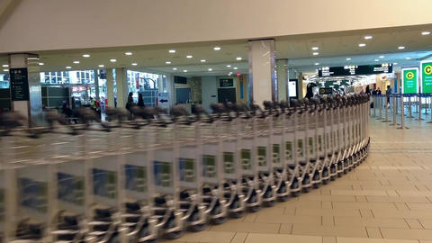 Airport workers moving stacks of luggage carts Footage
