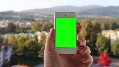 Man Holds A Blank Smart Phone With A Green Screen  stock footage