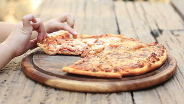 Close Up Child Hand Eating Pizza On Wood Table stock footage