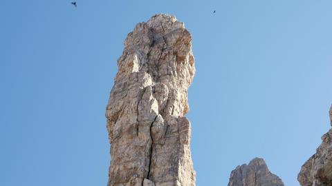 4k UHD tilt huge monolith with circling raven 1150 Footage
