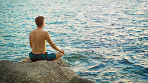 Man practicing yoga on the seashore Live Action