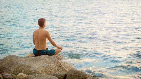 Young man practicing yoga. Sits in a lotus positio Footage