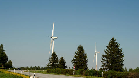 Two windmills and pine trees beside the road FS700 Footage