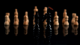 Black chess piece falling beside other pieces Live Action
