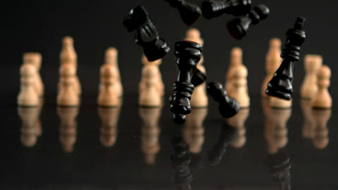 Black chess pieces falling on black background with white pieces Footage