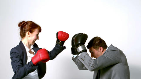Young businesswoman punching colleague with boxing gloves Footage