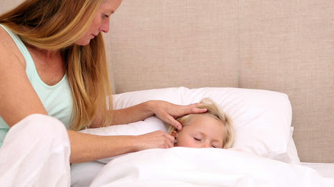 Mother taking the temperature of sick daughter Footage