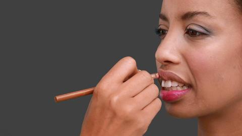 Make up artist putting lip gloss on models face Live Action