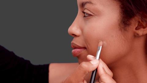 Make up artist putting foundation on models face Live Action