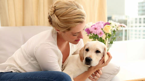 Happy Blonde Playing With Puppy On The Couch stock footage