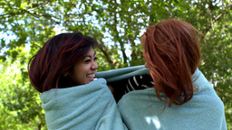 Pretty friends wrapped up in blanket Live Action