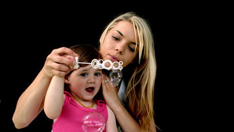 Cute little girl blowing bubbles with mother Footage