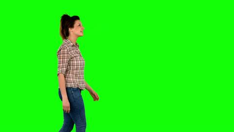 Casual brunette walking on green screen Footage