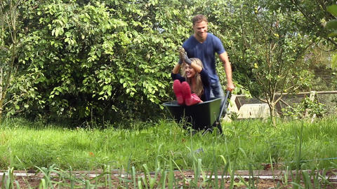Attractive young couple messing around with wheelbarrow Footage