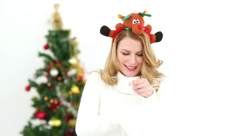 Festive blonde smiling at camera showing gift Footage