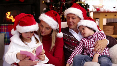 Happy family reading a christmas story together Footage