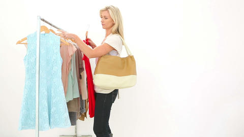 Pretty blonde looking through clothes rail Footage