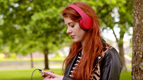 Pretty redhead listening to music in the park Footage