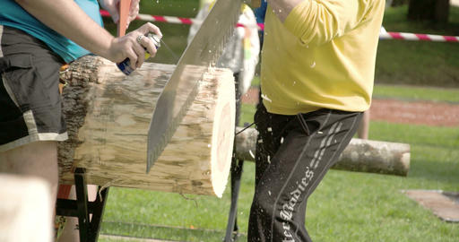 Two Men Are Trying To Cut The Big Log With The Saw stock footage