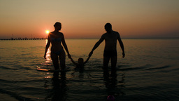 Family Of Three Coming Out Of Sea At Sunset Footage