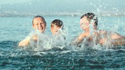 Family Of Three Splashing Water In Sea