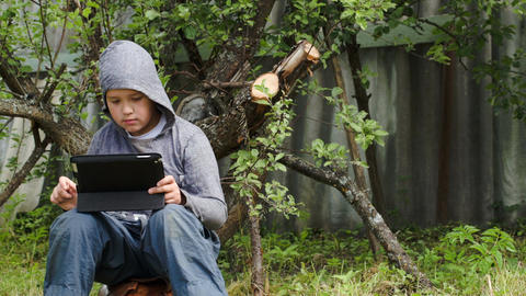 Teenager using tablet computer in the yard Footage