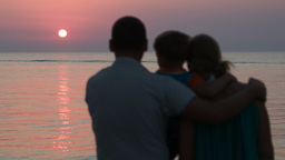 Family of three watching sunset over sea Footage