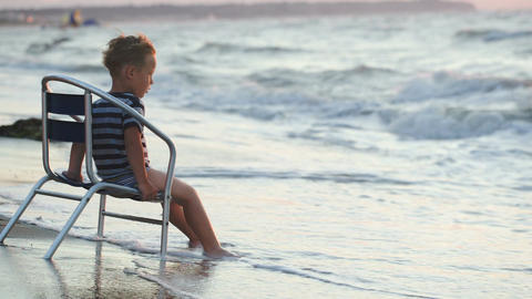 Boy sitting on the chair by sea, waves washing his Footage