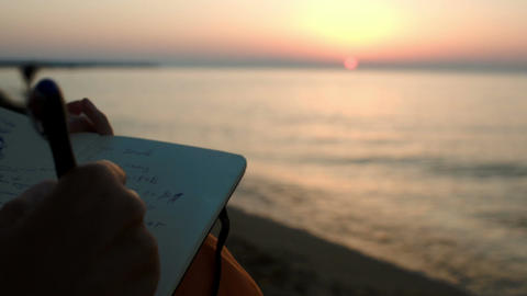 Woman making notes sitting by sea at sunset Footage