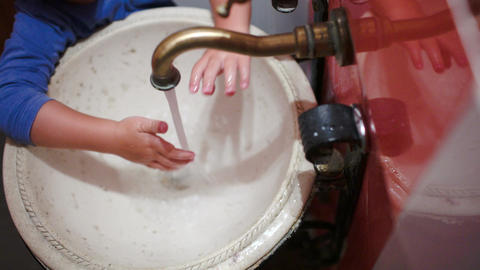 Child washing hands in vintage sink Live Action