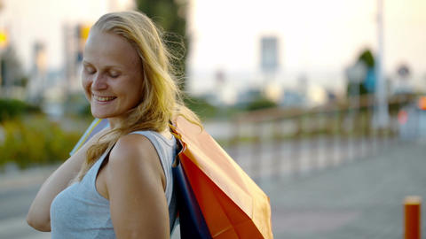 Smiling woman with shopping bags outdoor Footage