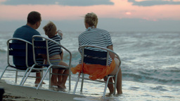 Family of three sitting on chairs by sea at sunset Footage