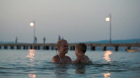 Mother helping son to jump in water Footage