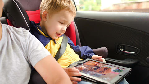 Happy boy playing game on pad during car travel Footage