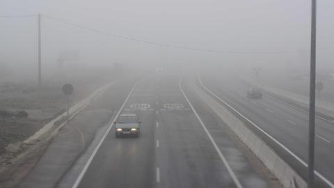 Cars drive in dense fog Footage