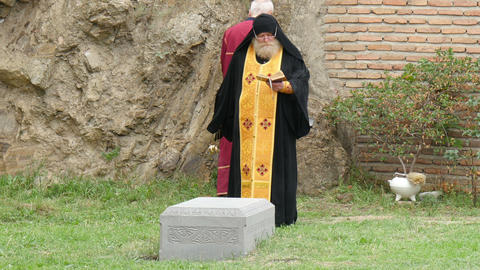 orthodox priest celebrating ceremony at burial in Footage