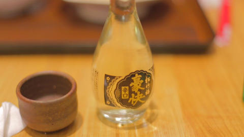 close sake bottle and cup to bowl of rice Footage