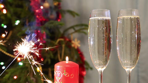Glasses With Champagne, Candle And Sparkler Agains stock footage