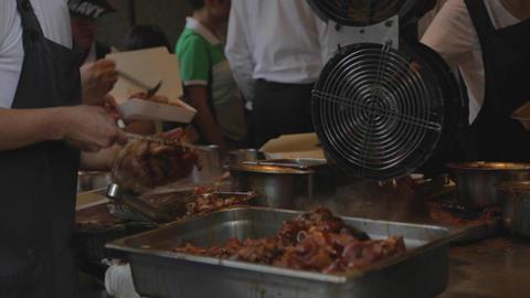 man cuts taiwan pork knuckle- close angle Live Action