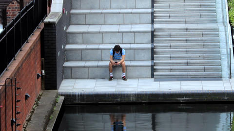 Boy with a cell phone sitting by the canal Footage