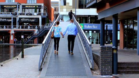 Young Couple Holding Hands Walking Through Footbri stock footage