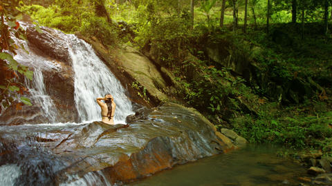 A woman bathes in the forest waterfall Footage