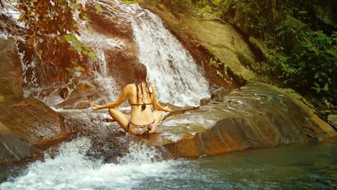 Woman meditating near a tropical waterfall. Thaila Footage