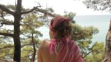 Young Woman Sits On A Cliff Against Sea stock footage