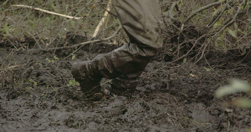 A man in boots walking onto the thick mud FS700 4K Footage